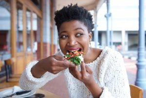 Happy young woman eating pizza at restaurant